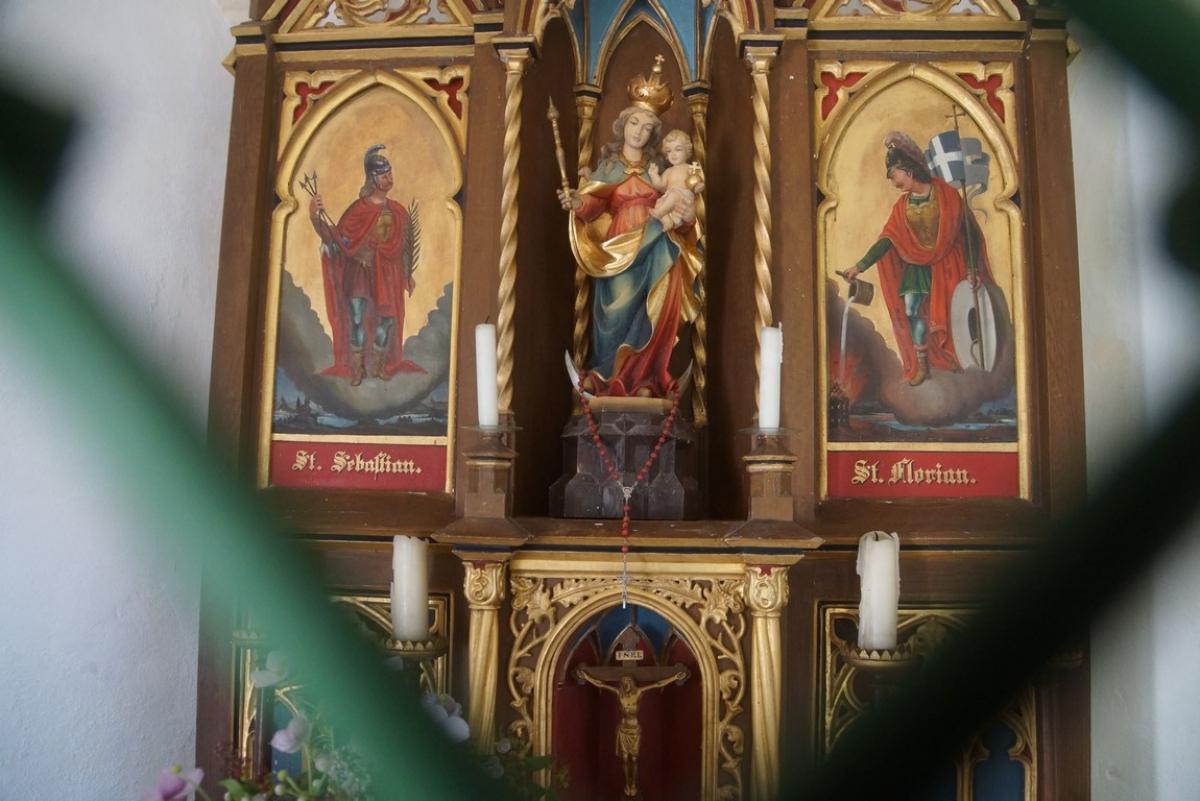 Ein kunstvoller Altar samt Aufsatz, in dem eine Muttergottes-Statue mit Kind thront, flankiert von den Heiligen Sebastian und Florian, schmückt die Stupper-Kapelle in Untermoosen.