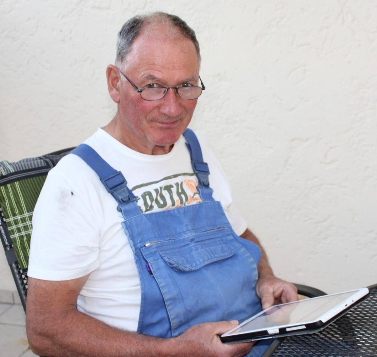 Felix Hagenauer sen. aus Reit informiert sich auf seinem Tablet über aktuelle Entwicklungen. Schmunzelnd erzählt er, dass er 1998 der erste Milchbauer in Saaldorf-Surheim war, der auf Bio umgestellt hat und dafür ziemlich belächelt wurde.