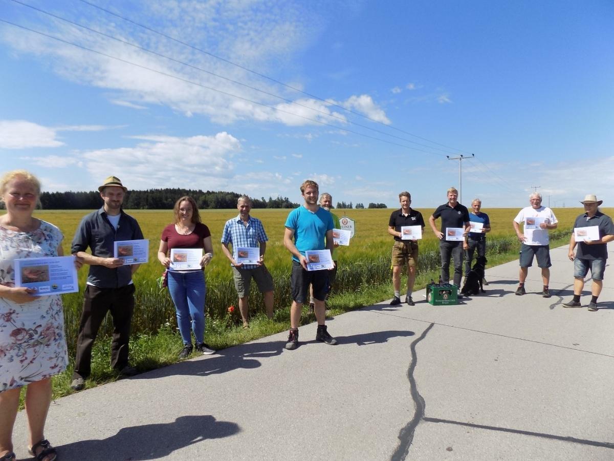 Als Zeichen der Anerkennung verteilte die Projekteiterin der Ökomodellregion, Marlene Berger-Stöckl (links), an die beteiligten Landwirte, Verarbeiter und Unterstützer eine Urkunde (5. von links: Landwirt Georg Planthaler).