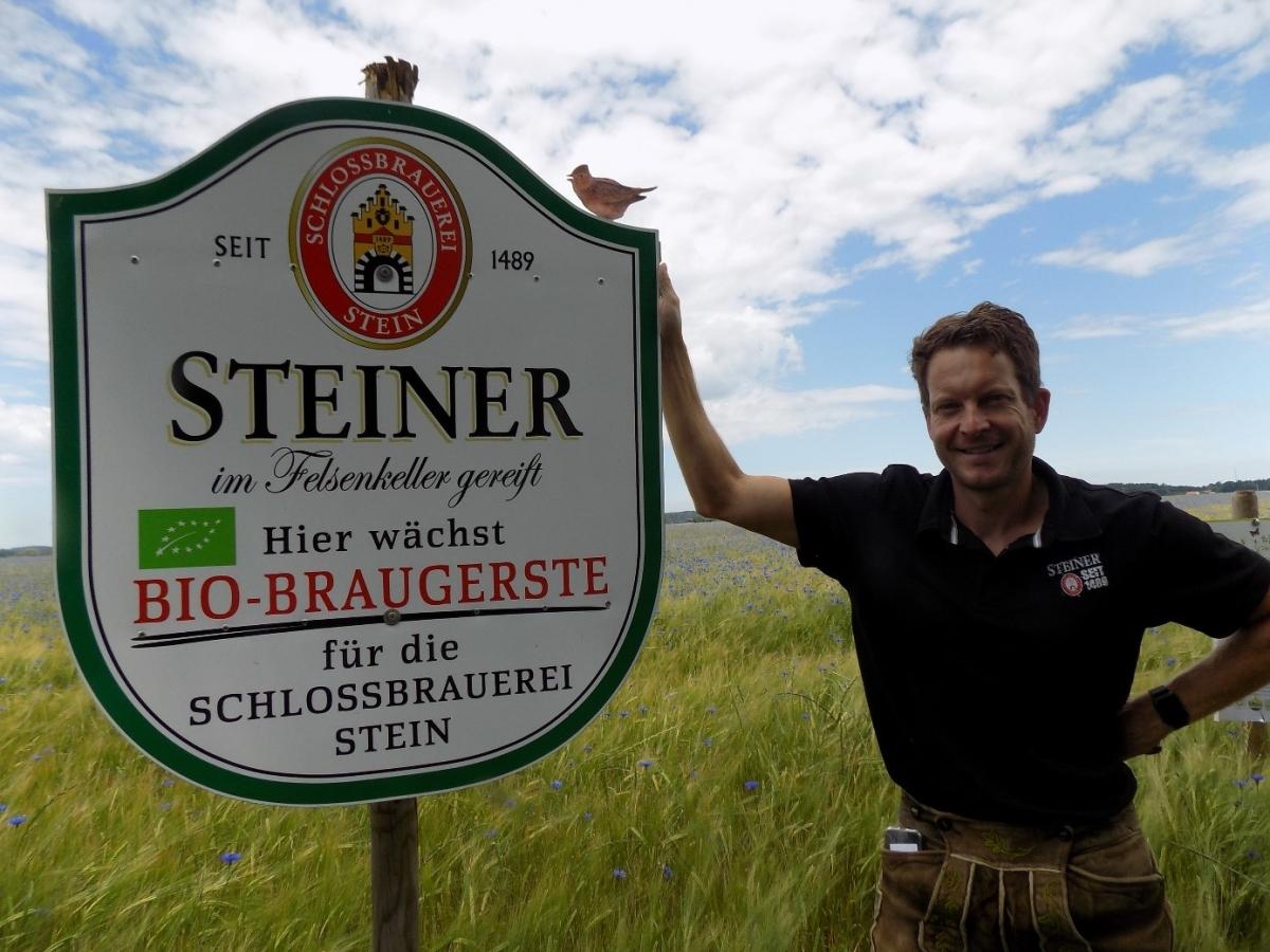 Stolz verweist der Vertriebsleiter der Schlossbrauerei Stein, Christian Eder, auf die Lerche, die auf dem Feldschild sitzt. Die Brauerei steht zu ihrer Bio-Gersten-Liefergemeinschaft mit 17 Bio-Betrieben aus der Ökomodellregion Waginger See.