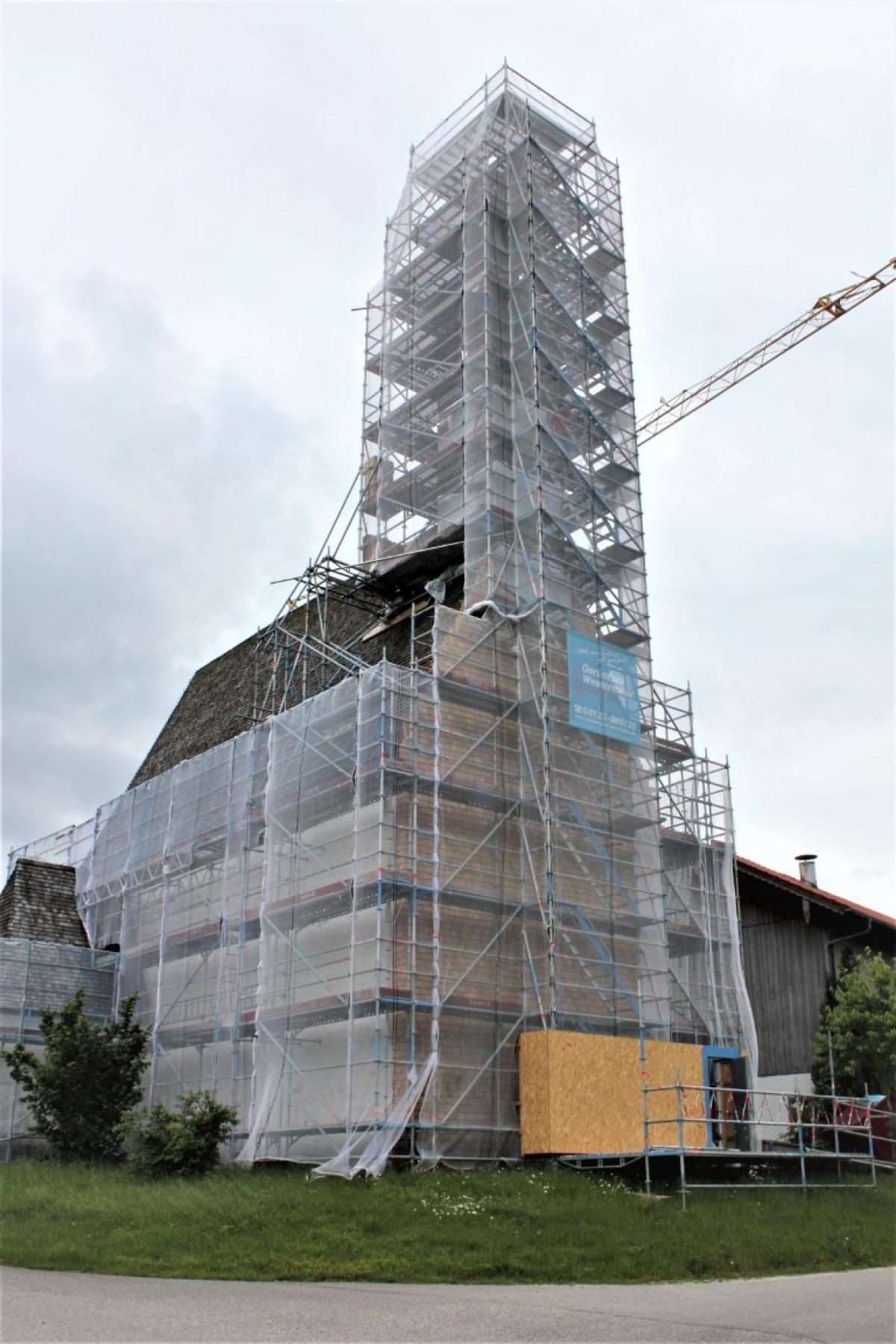 An der Turmseite der Kirchhallinger Kirche sind bereits neue Holzschindel angebracht worden, was durch das am Gerüst angebrachte Netz nur schemenhaft zu sehen ist.